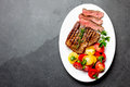Sliced medium rare grilled beef steak served on white plate with tomato salad and potatoes balls. Barbecue, bbq meat Royalty Free Stock Photo