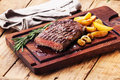 Sliced medium rare grilled steak ribeye beef with roasted potato wedges on cutting board on wooden background Royalty Free Stock Photos