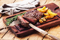 Sliced medium rare grilled steak ribeye beef with roasted potato wedges on cutting board on wooden background Stock Images