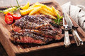 Sliced medium rare grilled steak ribeye with french fries black angus on serving board block Stock Images