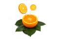 Sliced orange fruit with orange lollipops on green leaves isolated on white background Stock Photography