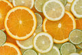 Sliced orange lemon and limes background made from lime citrus fruits Stock Images