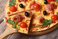 Sliced pizza with prosciutto tomatoes and arugula closeup ham black olives horizontal Royalty Free Stock Images