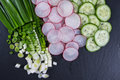 Sliced radish, Cucumber, Green onion on the black slate board. Ingredients for vitamin spring salad Royalty Free Stock Photo
