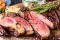 Sliced rare grilled or barbecued tomahawk beef steak on a griddle with fresh rosemary and tomato in a close up view. Royalty Free Stock Photo