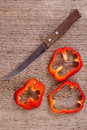 Sliced red bell peppers and old knife Royalty Free Stock Photo