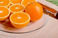 Sliced ripe appetizing orange on a cutting board on a green tabl Royalty Free Stock Photo