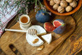 Sliced round of soft ripe creamy French Camembert cheese served with fresh juicy ripe red figs, honey and walnuts on a wooden back Royalty Free Stock Photo