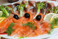 Sliced salmon a plate of with lemon herbs and olives Royalty Free Stock Image