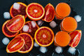 Sliced Sicilian red oranges and orange juice in small glasses on black stone background. Top view Royalty Free Stock Photo