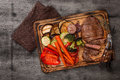 Sliced steak with grilled vegetables and sauce on wooden board