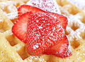 Sliced sugared strawberry on a waffle and strawberries macro with selective focus Royalty Free Stock Images