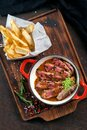 Sliced tenderloin steak medium rare with sauce on a plate and French fries Royalty Free Stock Photo