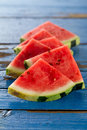 Sliced watermelon closeup. Many slices on an old rustic blue tab
