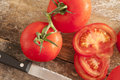 Sliced and whole fresh tomatoes on the vine Royalty Free Stock Photo
