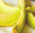 Sliced yellow melon on white plate Royalty Free Stock Photo