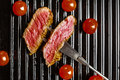 Slices of beef steak on meat fork and cherry tomatoes Royalty Free Stock Photo