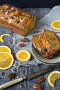 Slices of citrus cake on plate on rustic table with pecan walnuts orange slices and knife Stock Photo