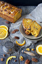 Slices of citrus cake on plate on rustic table with pecan walnuts orange slices and vintage strainer Stock Photo