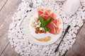 Slices of ham, walnuts and cheese on a plate. A knife and fork near a dish on a white stones background. Luxury dinner. Royalty Free Stock Photo