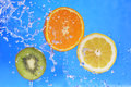 Slices of kiwi orange and lemon in water with bubbles Royalty Free Stock Image
