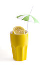Slices of lemon in yellow ceramic cup with a straw and umbrella Stock Image