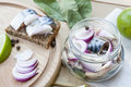 Slices of marinated mackerel with onion in a jar, lime, laurel and bread on wooden board Royalty Free Stock Photo