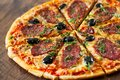 Pizza with Mozzarella cheese, salami, pepper, pepperoni, olives, Spices and Fresh Basil. Italian pizza on wooden background Royalty Free Stock Photo