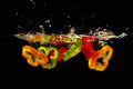 Slices of red, green and yellow pepper in water Royalty Free Stock Photo
