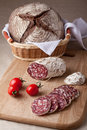 Slices salami on board, tomatoes, bread in basket Royalty Free Stock Photography
