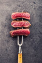 Slices of sirloin beef steak on meat fork on concrete background Royalty Free Stock Photo
