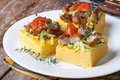 Slices of tasty polenta with meat and vegetables on a white plate on the table horizontal Stock Photo