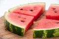 Slices of watermelon arranged on the wooden board Stock Photos
