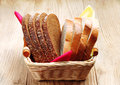 Slices wheat and rye bread in a basket on an old green table Stock Images