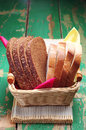Slices wheat and rye bread in a basket on wooden table Royalty Free Stock Image