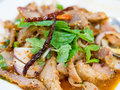 Slide grilled pork salad or Nam Tok garnish with mint leaves and dried chili. Nam Tok is spicy Northeast food of Thai flavors Royalty Free Stock Photo