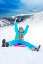 Sliding on sled from the slope happy girl downhill with her hands lifted wearing ski mask with mountains background Stock Images