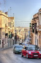 Sliema malta old city central street at sunny day of town in colorful cars balcons and blue sky Stock Photo