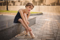 Slim ballerina in a blackdress putting on pointe shoes outdoor young Royalty Free Stock Photos