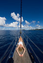 Slim blonde woman lays on prow of a sailing ship blue sky blue ocean white clouds over the tall and beautiful wide angle image Stock Photos