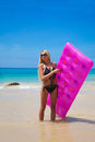 Slim blonde woman with pink swimming mattress on tropical beach Royalty Free Stock Photo