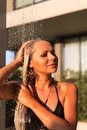 Slim blonde woman taking shower near pool outdoors Royalty Free Stock Photo