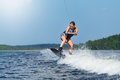 Slim brunette woman riding wakeboard on motorboat wave in lake Royalty Free Stock Photo