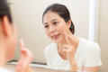 Slim female model applying foundation moisturizer