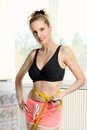Slim fit smiling blonde girl young woman measuring her waist Royalty Free Stock Photo