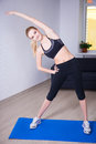 Slim flexible woman doing stretching exercise at home young Stock Image