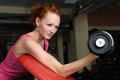 Slim girl doing biceps traning young red haired workout with dumbbell Royalty Free Stock Photography