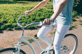 Slim girl in jeans and t-shirt sitting on the blue cruise bike o Royalty Free Stock Photo