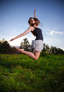 Slim girl jumping high on field beautiful Stock Photo