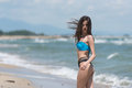 Slim girl in rear view wear bikini and walking on sandy beach Royalty Free Stock Photo